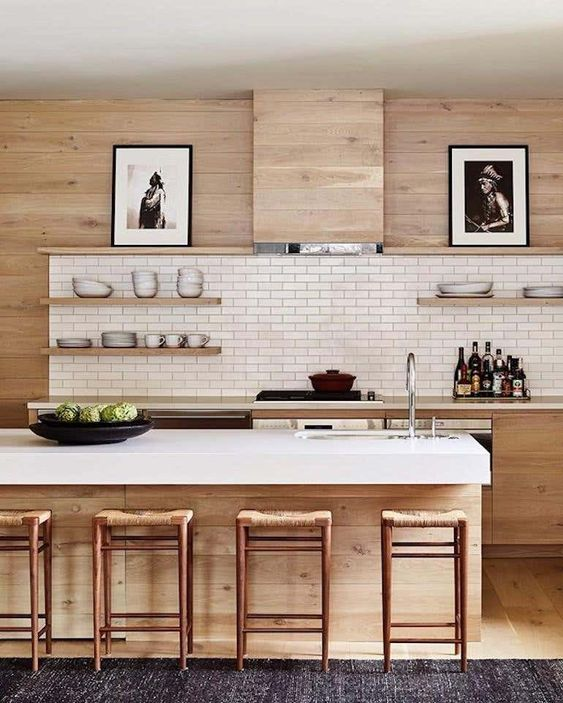 a light stained farmhouse kitchen with a hood that matches the wall, stone countertops and a white skinny tile backsplash