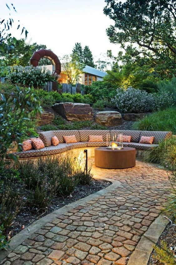 a welcoming backyard with a built-in bench, a contemporary fire pit and outdoor lamps for a stylish and cool look