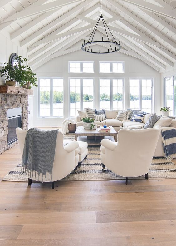 a beautiful coastal living room clad with white wood, with a stone fireplace, a low table and white furniture plus blue textiles