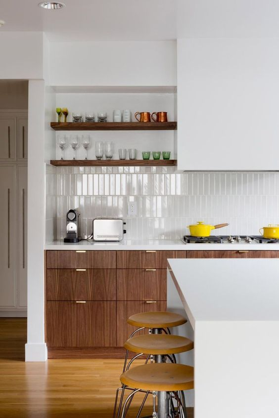 a mid-century modern kitchen with stained and sleek white cabinets and a hood, a skinny tile backsplash and built-in shelves