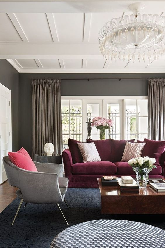 a refined living room with grey walls, a purple sofa, a grey chair, round and square coffee tables and a catchy crystal chandelier
