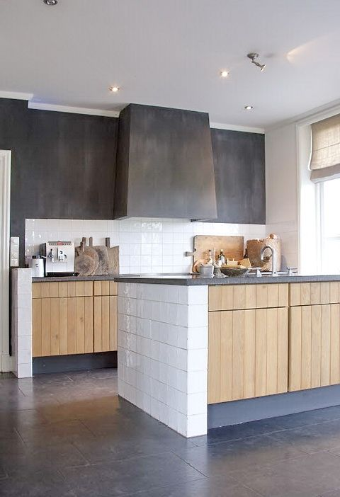 a modern kitchen with light stained wooden cabinets and concrete countertops, a concrete wall and an integrated hood is chic