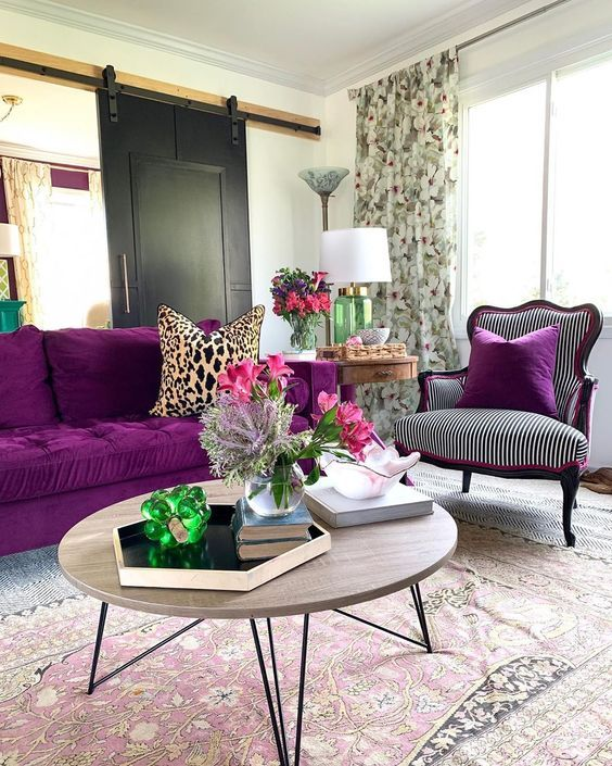 a refined modern living room with a barn sliding door, a bold purple sofa, a refined chair, a round table and floral curtains
