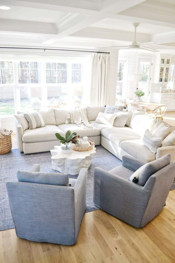 a stylish living room with a large white sectional, blue chairs and a rug and some baskets for storage and decor