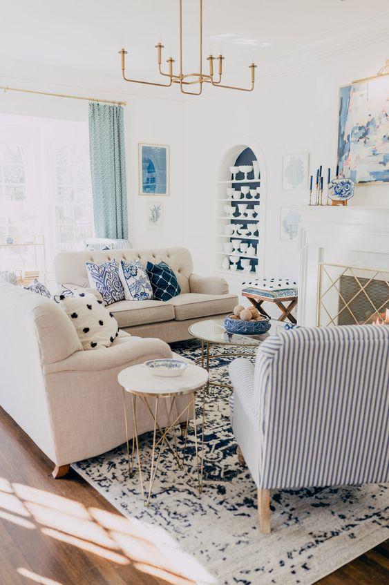 a catchy living room with a fireplace, neutral sofas, blue printed pillows and a striped chair, an elegant chandelier and a blue niche with tableware