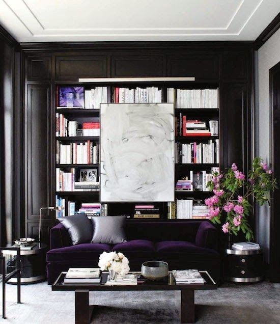 a refined modern monochromatic living room with built-in bookshelves, a deep purple velvet sofa for a color statement and a chic table