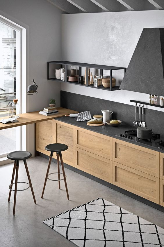 a stylish contemporary kitchen with light stained cabinets, black stone countertops, a backsplash and a hood looks chic