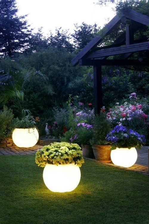lit up planters with blooms are a very creative way to light up your garden and bring a decorative value at the same time