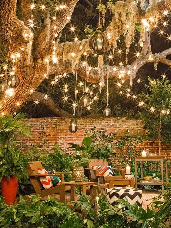 a backyard space with lots of string lights, rattan pendant lamps and candle lanterns all over the space is very cool