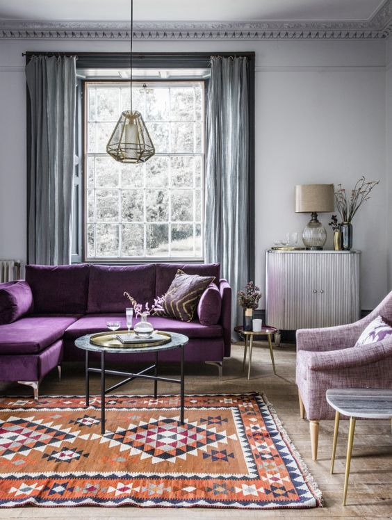 a serene living room with light grey walls, grey curtains, a purple sectional, a lilac chair and a printed rug