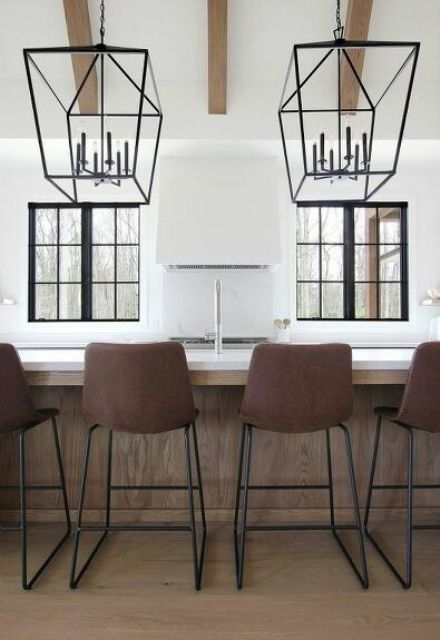 a stylish minimalist kitchen with white cabinets, a matching hood that looks seamless, brown stools and pendant lamps