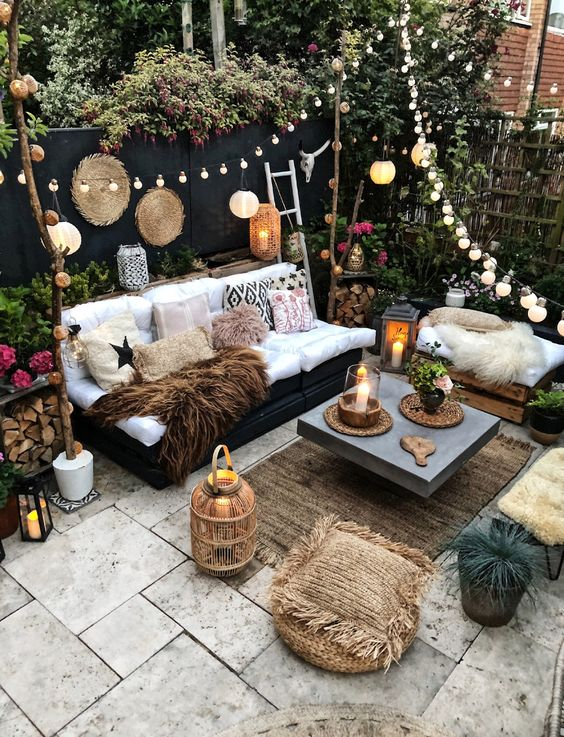 a boho backyard with candle lanterns, string lights and paper lamps over the space, potted blooms and greenery around
