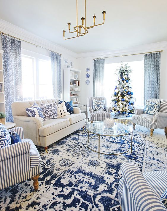 a glam blue and white living room with a white sofa and striped furniture, printed pillows and a rug, blue curtains and a gold chandelier