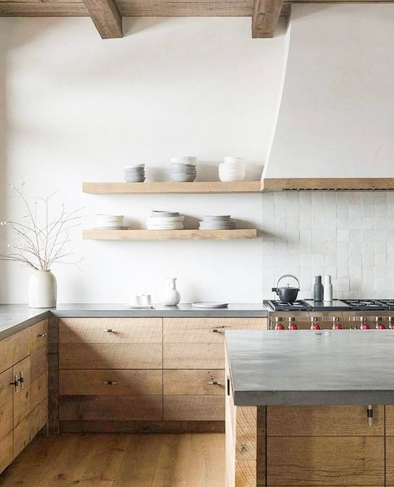 a serene minimalist kitchen with stained rough cabinetry, concrete countertops, a white hood and a white tile backsplash looks ethereal
