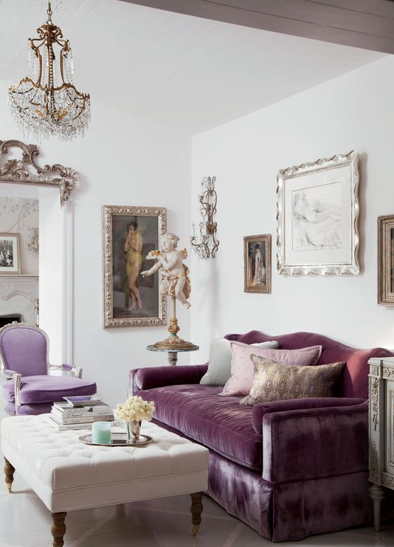 a sophisticated neutral living room with a purple sofa and a lilac chair, a creamy tufted ottoman and a very exquisite gallery wall
