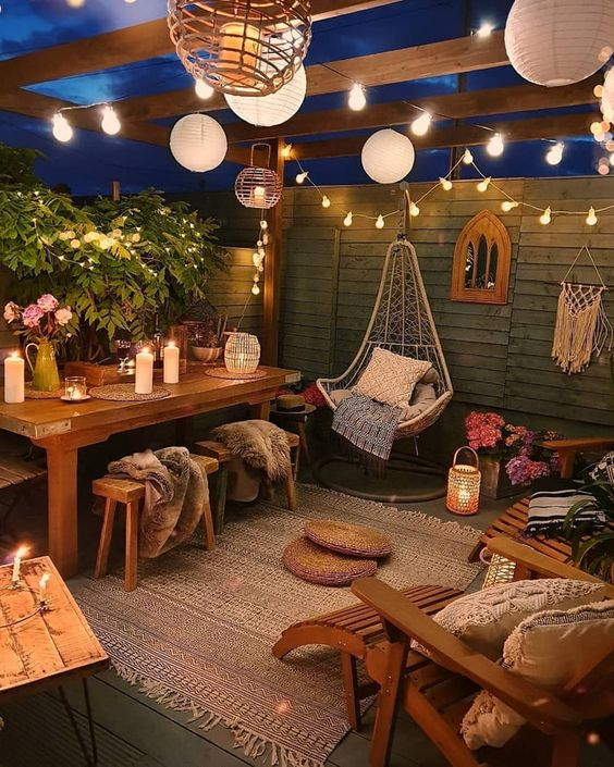 a relaxed and welcoming boho backyard with paper and string lights, with candles and candle lanterns