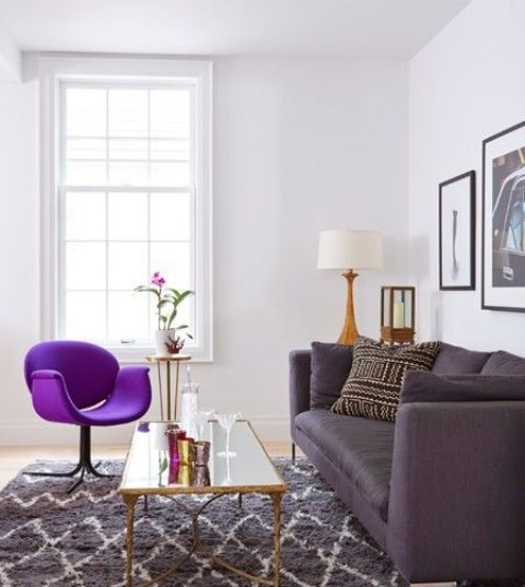 a stylish living room in neutrals, with a grey printed rug, a deep purple sofa, a bold purple chair, a chic gallery wall and a mirror table