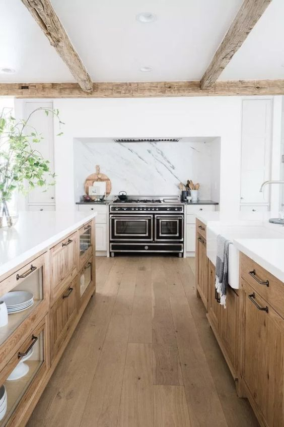 an elegant modern farmhouse kitchen with light stained cabinets, white stone countertops and an integrated hood over the cooker