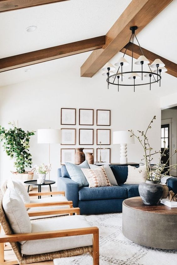 a chic farmhouse living room with wooden beams, a navy sofa, neutral chairs, a round coffee table and a gallery wall