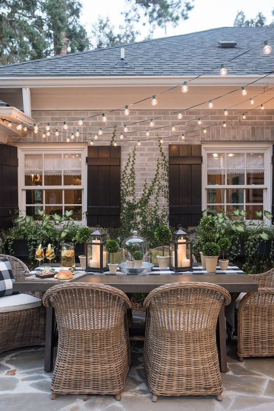 a stylish backyard dining space with a wooden table and rattan chairs and string lights over the space
