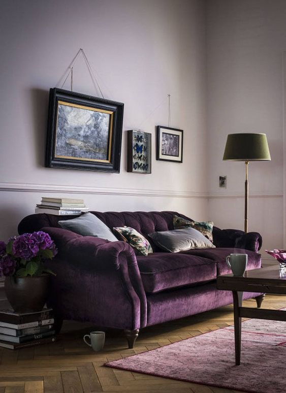 a welcoming living room with lilac walls, a refined purple velvet sofa, a lilac rug, a vintage gallery wall, a green floor lamp and a dark stained table
