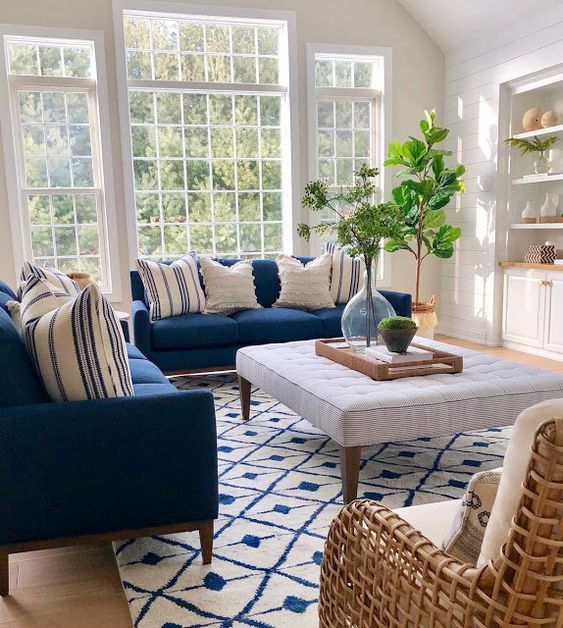 38 a beautiful coastal living room with navy sofas, a striped ottoman, white built-in storage units and a white rattan chair