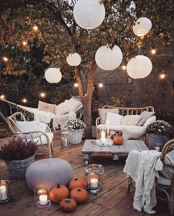 a welcoming backyard with candle lanterns, strign lights over the space and paper lamps is amazing and cozy