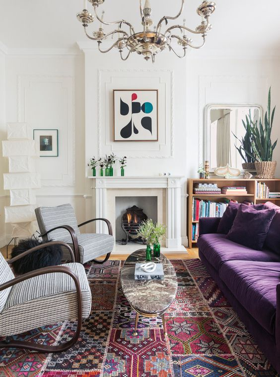 an eclectic living room with a non-working fireplace, a depe purple sofa, printed chairs, a refined chandelier and a bold printed rug