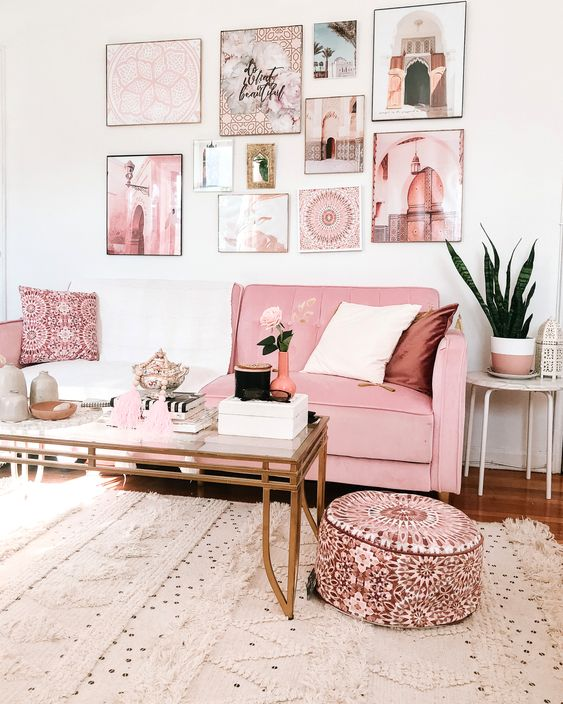 a glam living room with a pink sofa and ottoman, a pink gallery wall, a glass coffee table and a Moroccan rug
