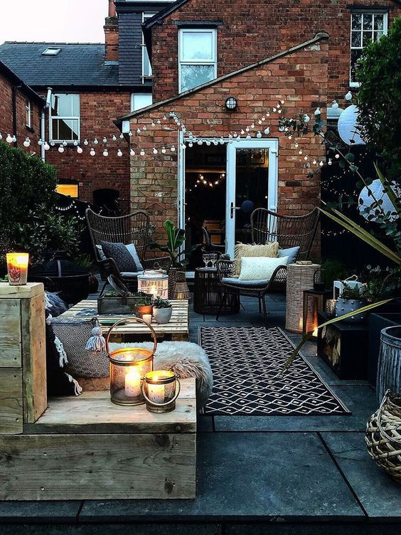 a welcoming backyard with pallet and rattan furniture, with printed textiles, candle lanterns and string lights over the space