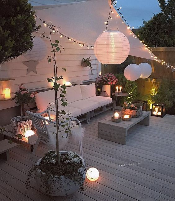 a welcoming deck with modern pallet and rattan furniture, candle lanterns, string lights and paper lamps over the space