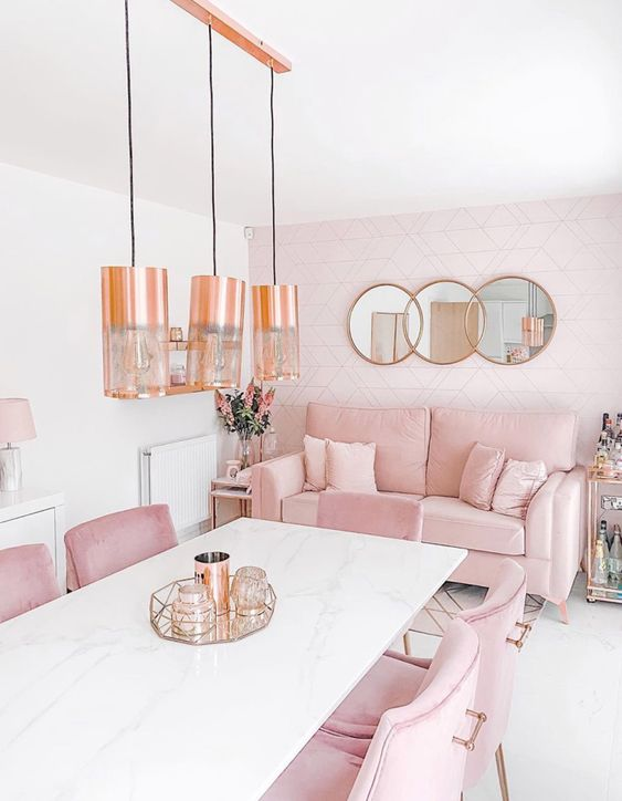 a chic dining room with a white stone table, pink chairs and a sofa, a blush accent wall, pendant lamps and round mirrors
