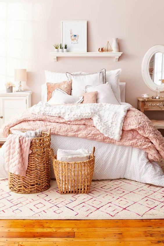 42 a lovely bedroom with a blush wall, neutral and stained furniture, baskets, a floatign shelf and pink textiles