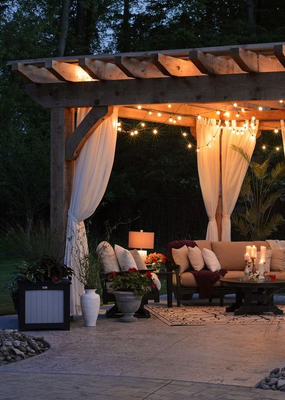 string lights, floor lamps and candles on the table make this outdoor living room very welcoming and very chic