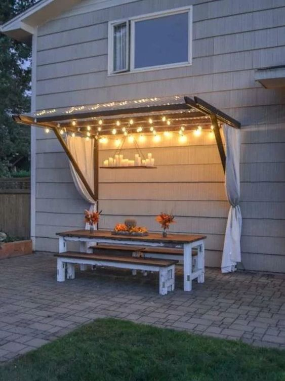 a backyard dining space with string lights over the space and a candle chandelier is a very cool and beautiful idea