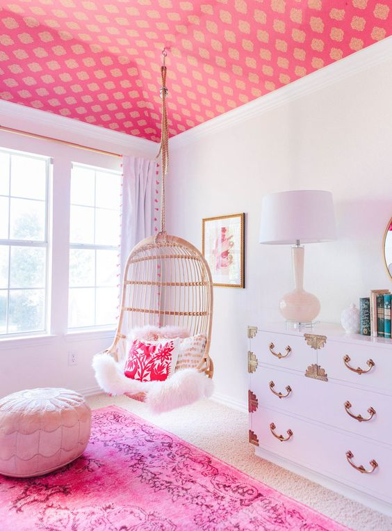 44 a glam space with a pink printed ceiling, a hot pink rug and pillow, a white dresser and an ottoman