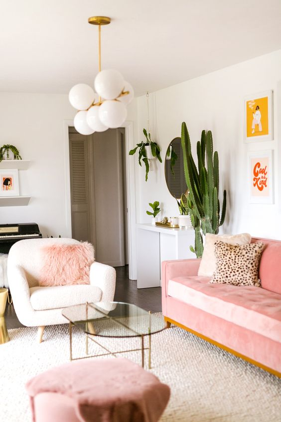 a pretty modern living room with a pink sofa, a stool and a faux fur pillow, potted plants, a retro chandelier and a glass table