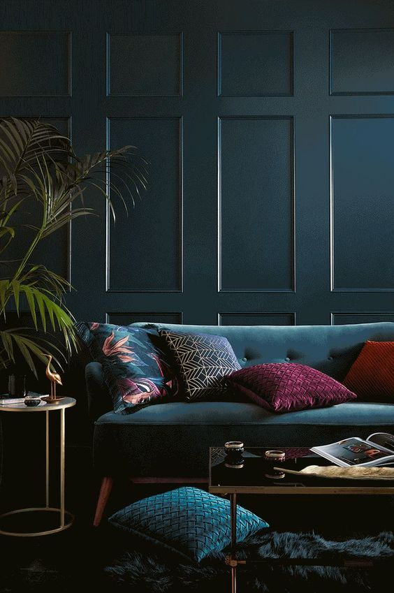 47 a modern and moody jewel tone living room with a teal panel wall, a teal sofa and pillows, a low table and potted plants