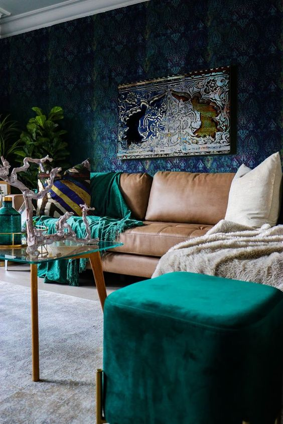 a sophisticated living room with a dark wallpaper wall, a brown sofa, emerald touches and a glass table plus potted plants
