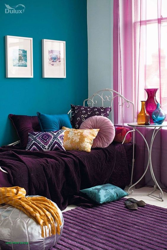 50 a bold boho nook with a teal wall, a daybed with purple, teal, mauve and yellow textiles, a purple rug and bold vases