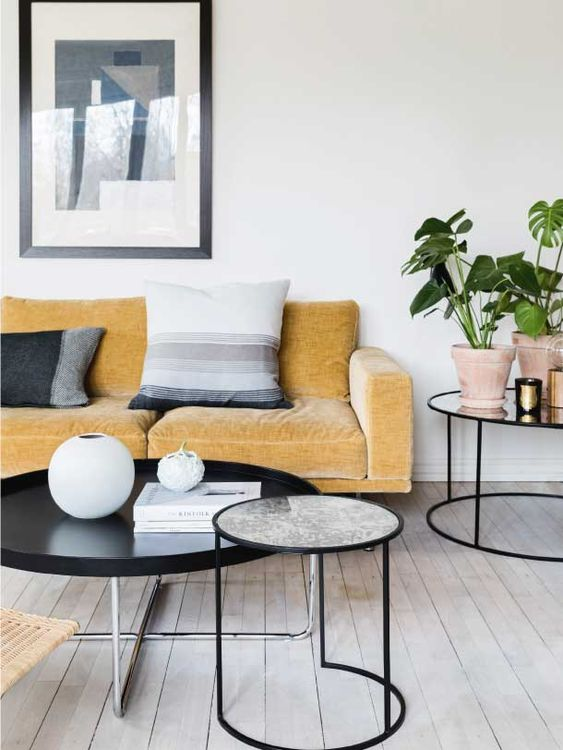 a Nordic living room with a yellow sofa and graphic pillows, round tables, potted plants and graphic art
