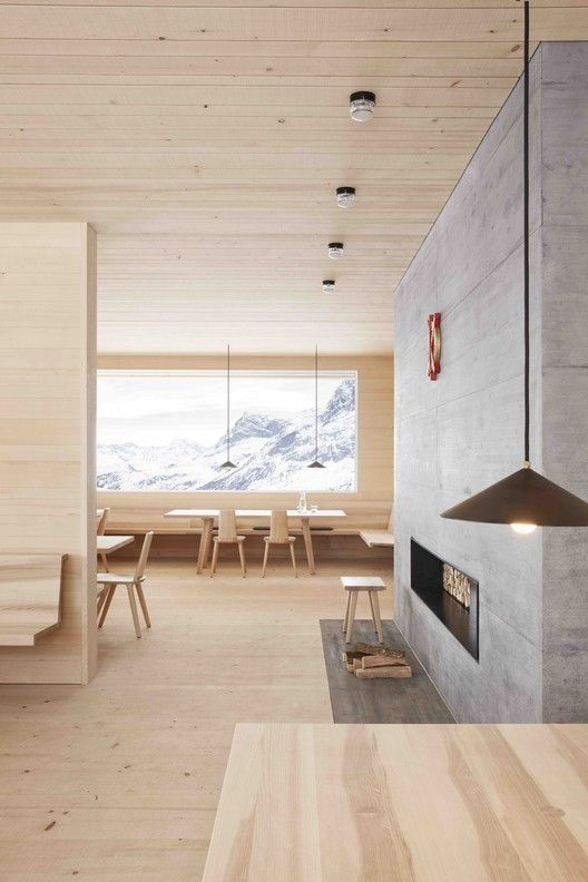 a beautiful chalet space fully clad with blonde wood including blonde wood furniture and a concrete clad fireplace