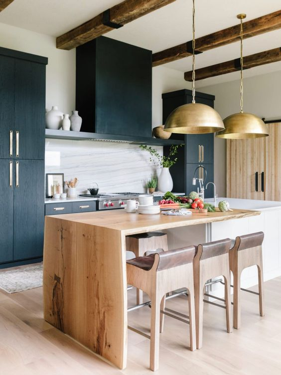 a beautiful kitchen with black cabinets, a white stone backsplash, a live edge blonde wood countertop and matching stools plus gold lamps