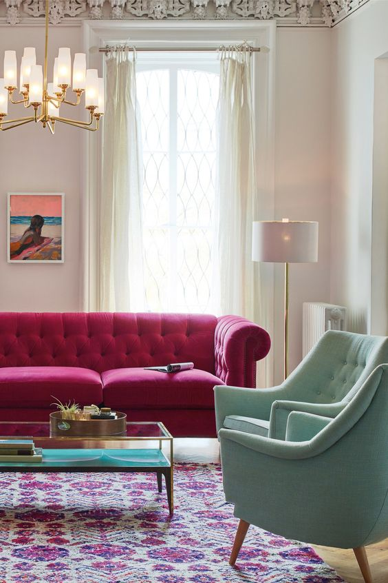 a beautiful living room with a hot pink sofa, pastel green chairs, a chic chandelier, a bold boho rug, a low table and neutral curtains