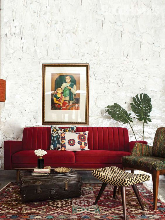 a beautiful living room with catchy walls, a deep red sofa, printed furniture and a rug and a vintage suitcase for storage