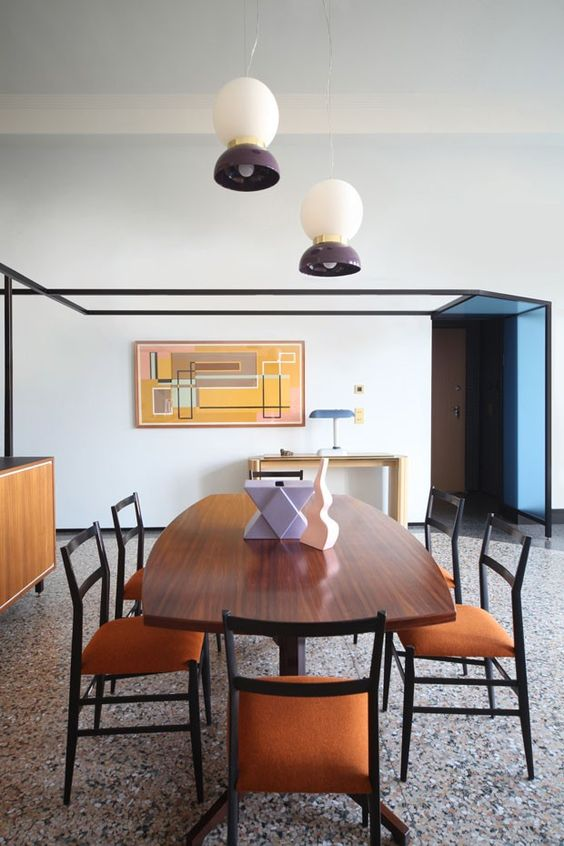 a beautiful mid-century modern dining room with a grey terrazzo tile floor, chic dining furniture and pendant lamps