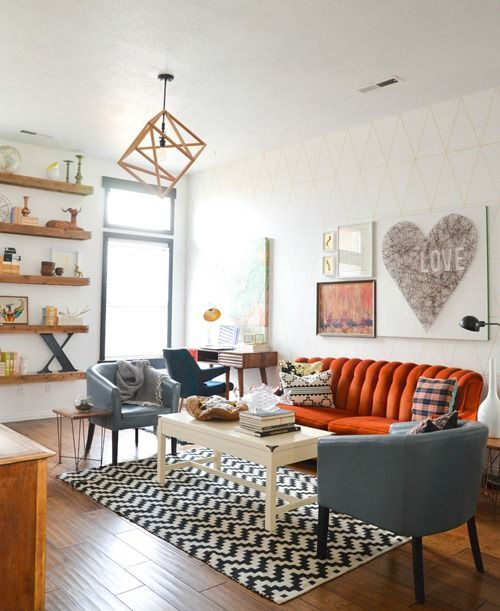a beautiful mid-century modern living room with floating shelves, an orange sofa, grey chairs, a low table and a geometric pendant lamp
