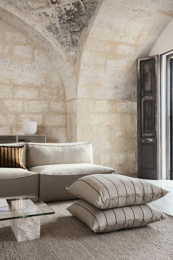 a beautiful neutral living room with a low creamy sofa, pillows, a marble and glass coffee table and stone walls