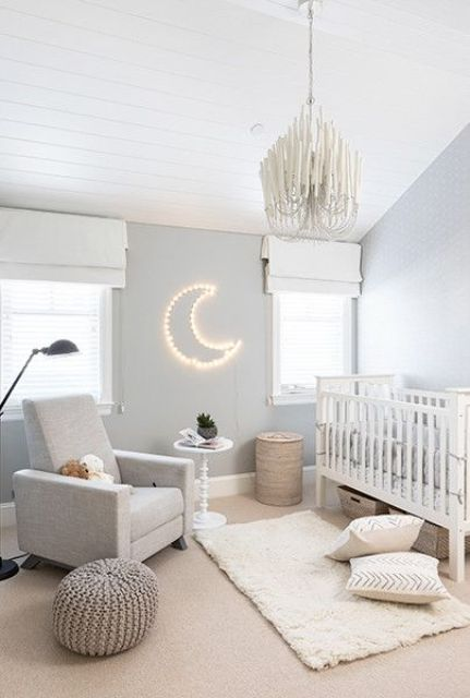 a beautiful neutral nursery with grey walls, grey and white furniture, printed pillows, a cool chandelier and a half moon lamp