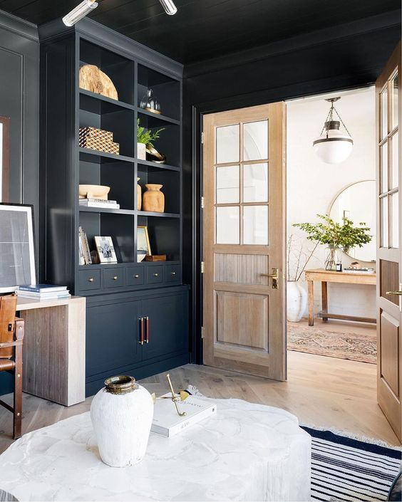 a black space with a blonde wood floor, doors and a desk looks more lightweight and more contrasting at the same time